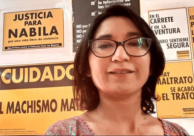 La abogada Silvana del Valle. Tiene el pelo hasta los hombros y lentes. En el fondo, hay afiches de la Red Chilena contra la Violencia hacia las Mujeres.
